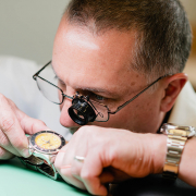 An employee looking at a watch repair at Spicer Greene Jewelers