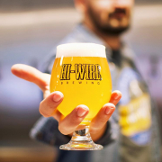 Brewer holding a Hi-Wire Brewing beer glass