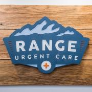 Range Urgent Care logo sign hanging on wood wall